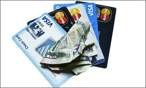 four credit cards and crumpled cash
